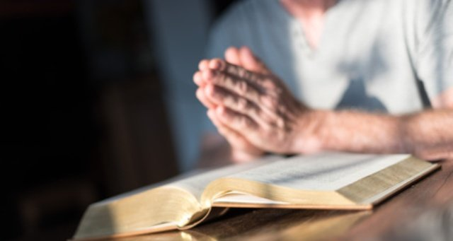 Man praying hands on a Bible