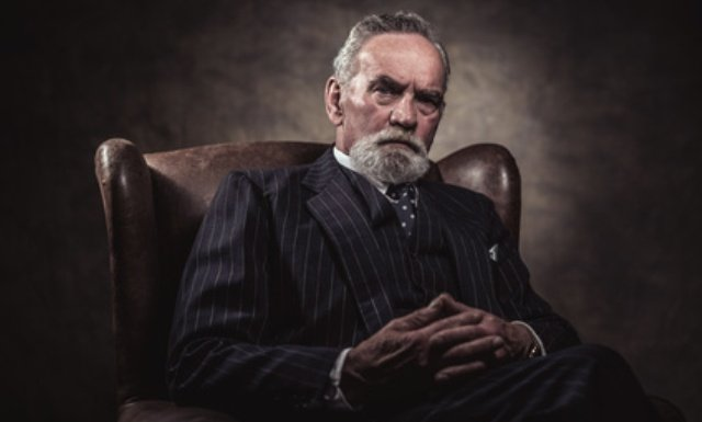 In chair sitting characteristic senior business man. Gray hair and beard wearing blue striped suit and tie. Against brown wall.