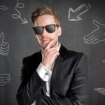 Narzissmus: Mann im Anzug mit Sonnenbrille vor schwarzer Wand mit Kreidezeichnungen