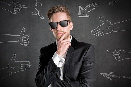 Narzisstischer Mann im Anzug mit Sonnenbrille vor schwarzer Wand mit Kreidezeichnungen